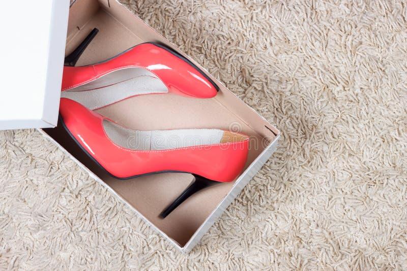 Rode vrouwenschoenen in doos stock foto's