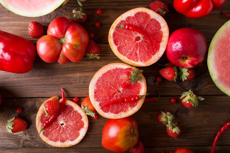 Rode vruchten en groenten op een houten achtergrond stock foto