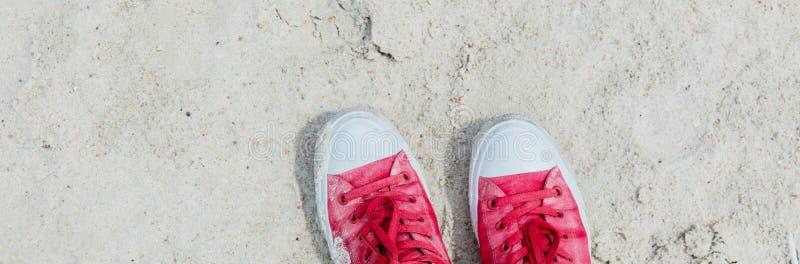 Rode vuile gumshoes op zand royalty-vrije stock afbeeldingen