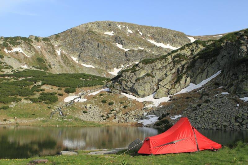 Rode wandelaartent dichtbij bergmeer stock foto's