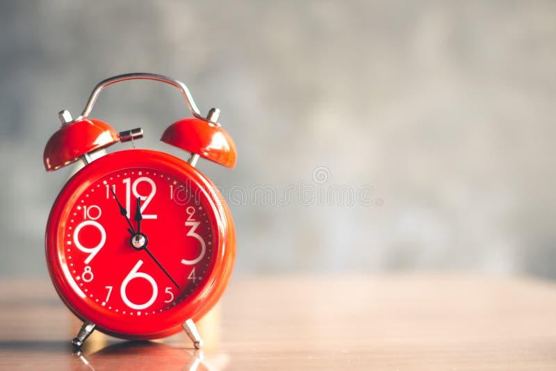 Rode wekker met vijf minuten aan de klok van twaalf o ` royalty-vrije stock fotografie