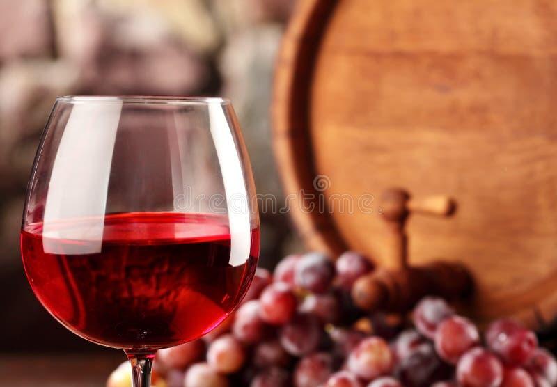 Rode wijn Close-upglas van rode wijn, druiven en vat Selectieve nadruk De atmosfeer van de wijnkelder De ruimte van het exemplaar royalty-vrije stock foto