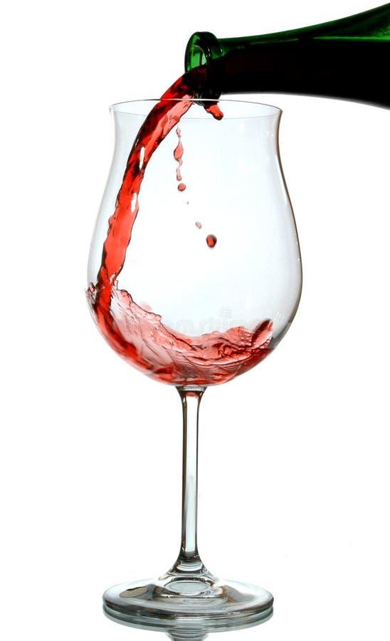 Rode wijn die in een wijnglas wordt gegoten royalty-vrije stock foto's