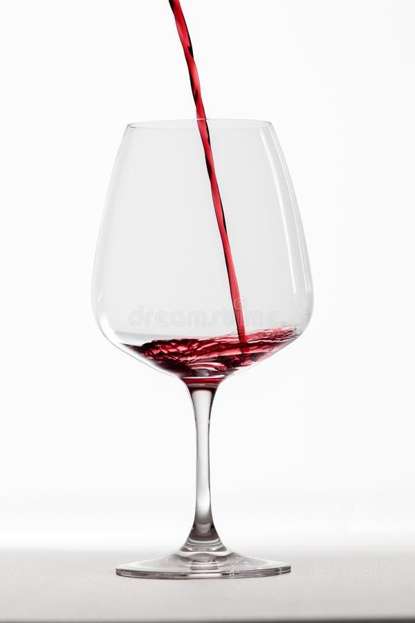 Rode wijn die in glas wordt gegoten royalty-vrije stock foto's