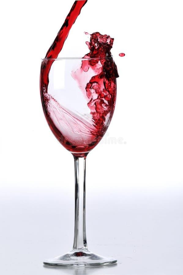 Rode wijn die op glas wordt gegoten royalty-vrije stock foto