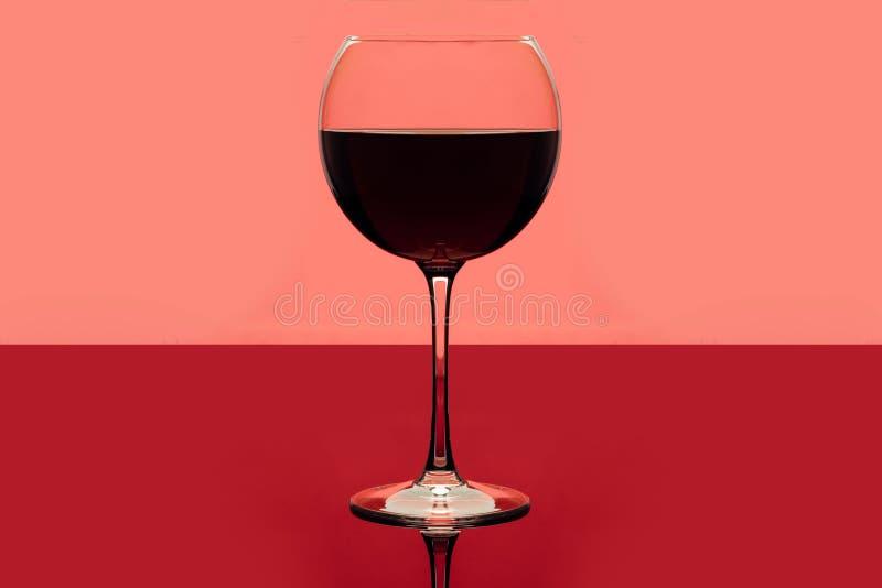 Rode wijn Drankglas rode wijn op een roze en rode achtergrond Alcoholische drank Romantische avond of eenzaamheid stock afbeeldingen