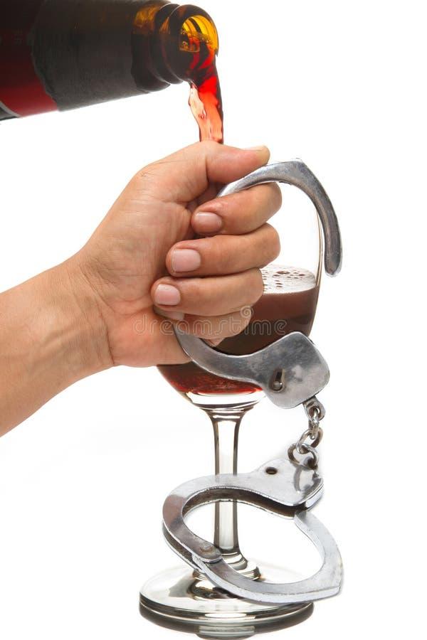Rode wijn in een wijnglas en handcuffs royalty-vrije stock foto