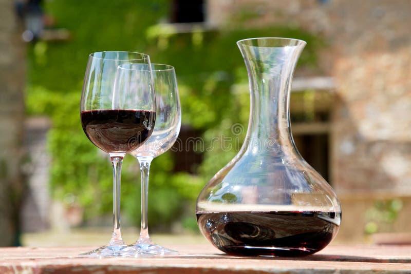 Rode wijn in een wijnkaraf en een twee wijnglazen stock foto