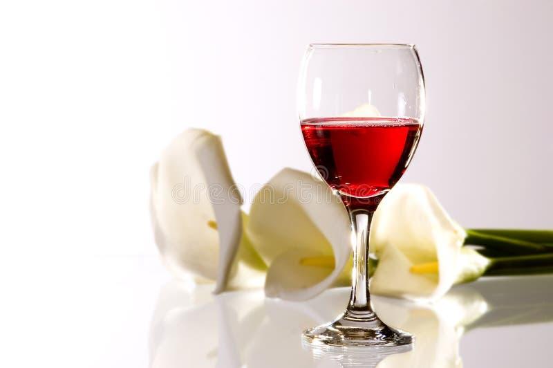 Rode wijn en bloemen stock foto