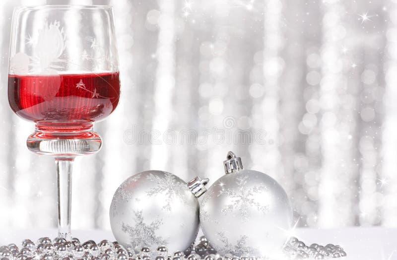 Rode wijn en Kerstmisballen tegen en vakantielichten stock afbeeldingen