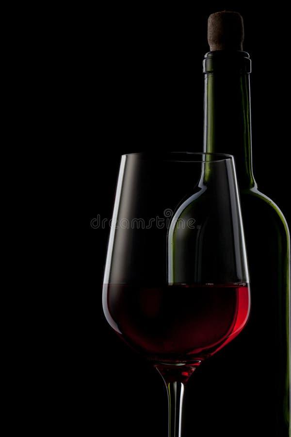 Rode wijn in glas en fles op zwarte stock foto