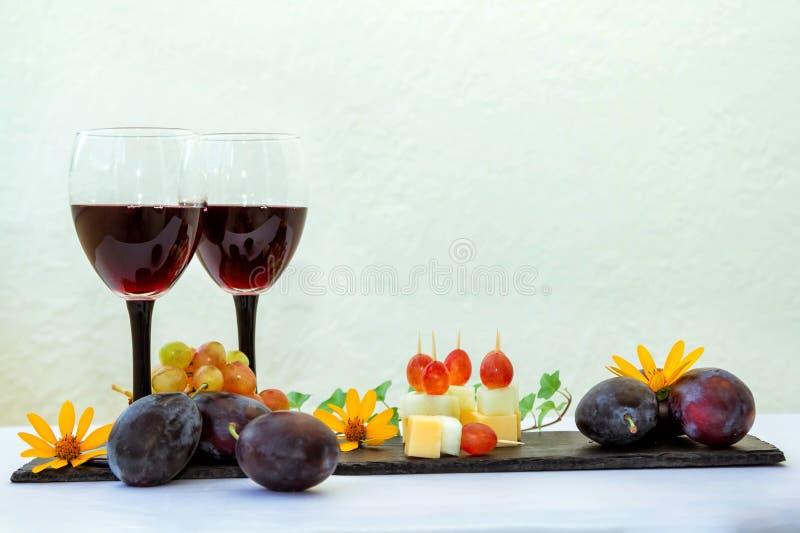 Rode wijn in glas, vruchten, zoete vleespennen en bloemen stock afbeeldingen