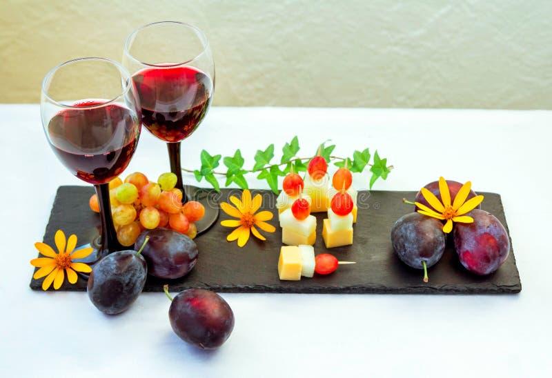 Rode wijn in glas, vruchten, zoete vleespennen en bloemen royalty-vrije stock foto's