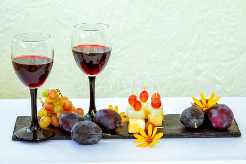 Rode wijn in glas, vruchten, zoete vleespennen en bloemen royalty-vrije stock afbeeldingen