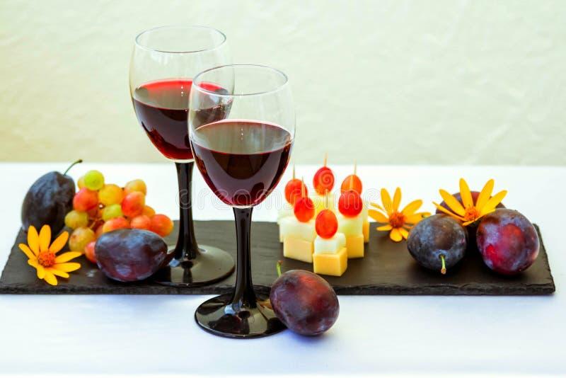 Rode wijn in glas, vruchten, zoete vleespennen en bloemen stock afbeelding