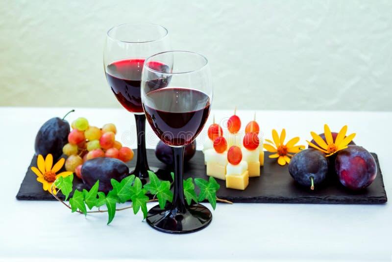 Rode wijn in glas, vruchten, zoete vleespennen en bloemen stock fotografie