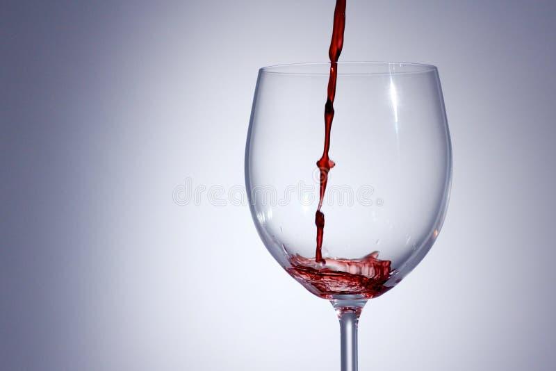 Rode Wijn het gieten in een glas met a met achtergrond royalty-vrije stock afbeelding