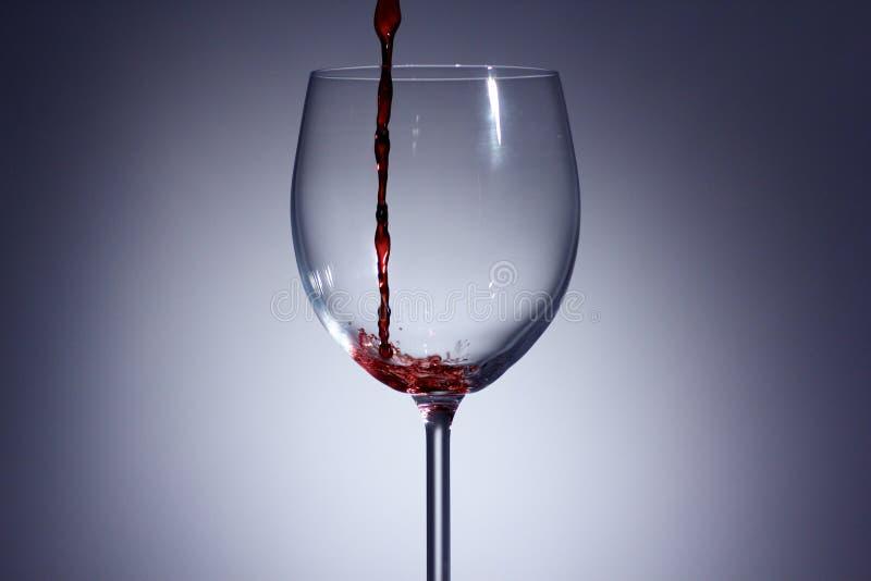 Rode Wijn het gieten in een glas met a met achtergrond stock foto's