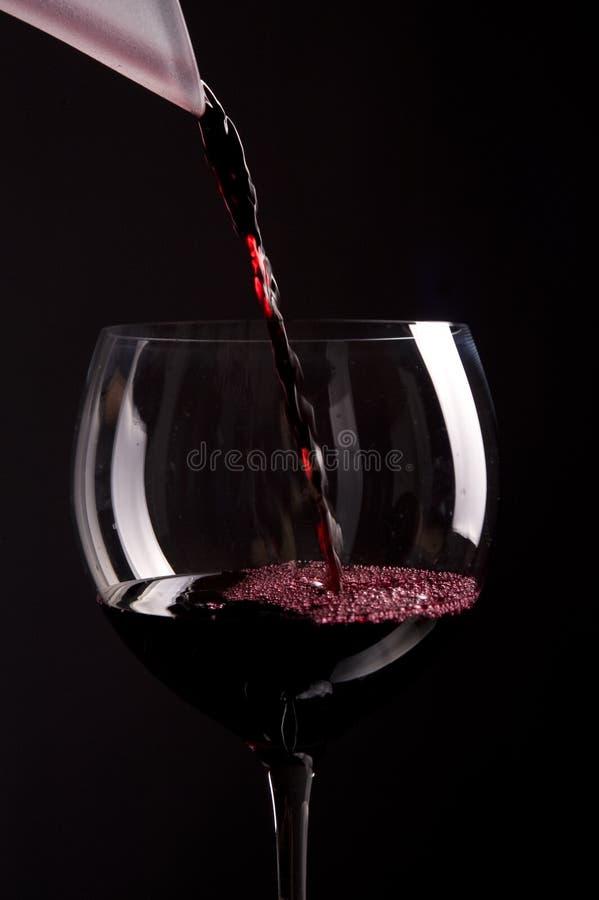 Rode wijn het gieten in glas stock afbeelding