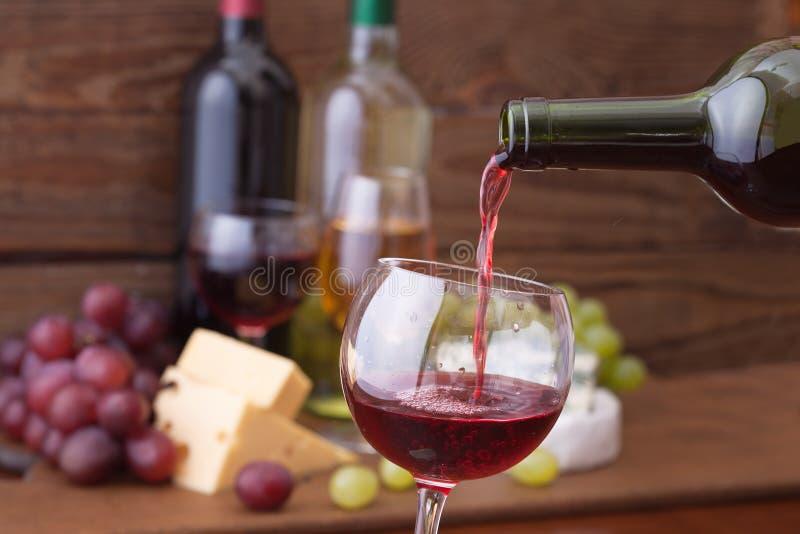 Rode wijn het gieten in glas, close-up stock afbeelding