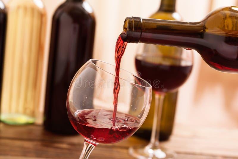 Rode wijn het gieten in glas, close-up royalty-vrije stock afbeelding
