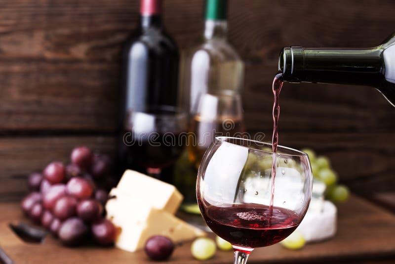 Rode wijn het gieten in glas, close-up stock fotografie