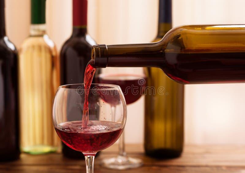 Rode wijn het gieten in glas, close-up stock afbeeldingen