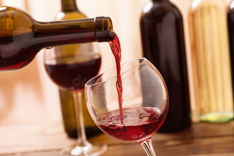 Rode wijn het gieten in glas, close-up stock foto's