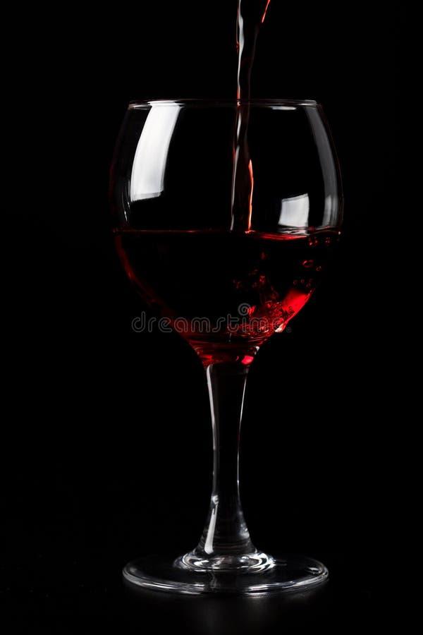 Rode wijn het gieten in glas over zwarte royalty-vrije stock fotografie
