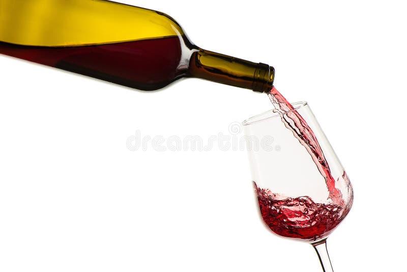 Rode wijn het gieten van fles in glas op een witte achtergrond stock fotografie