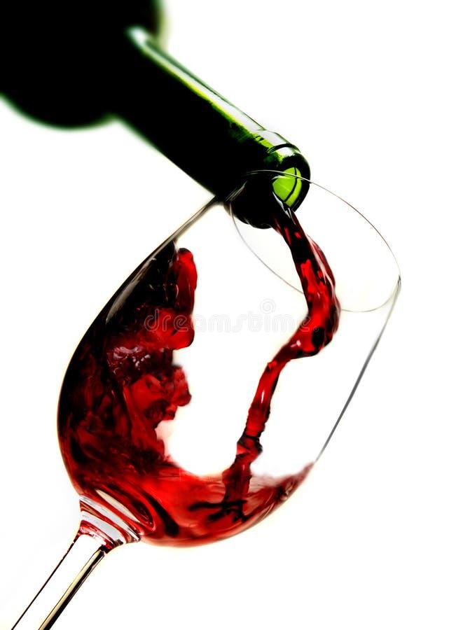 Rode wijn het gieten in wijnglas royalty-vrije stock afbeelding