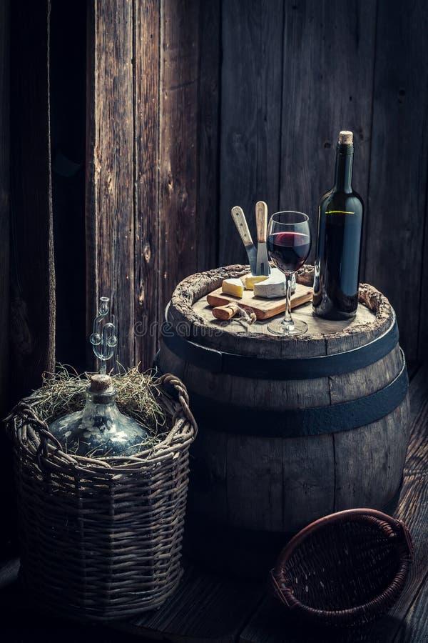 Rode wijn met kaas en korffles in kelderverdieping stock afbeeldingen