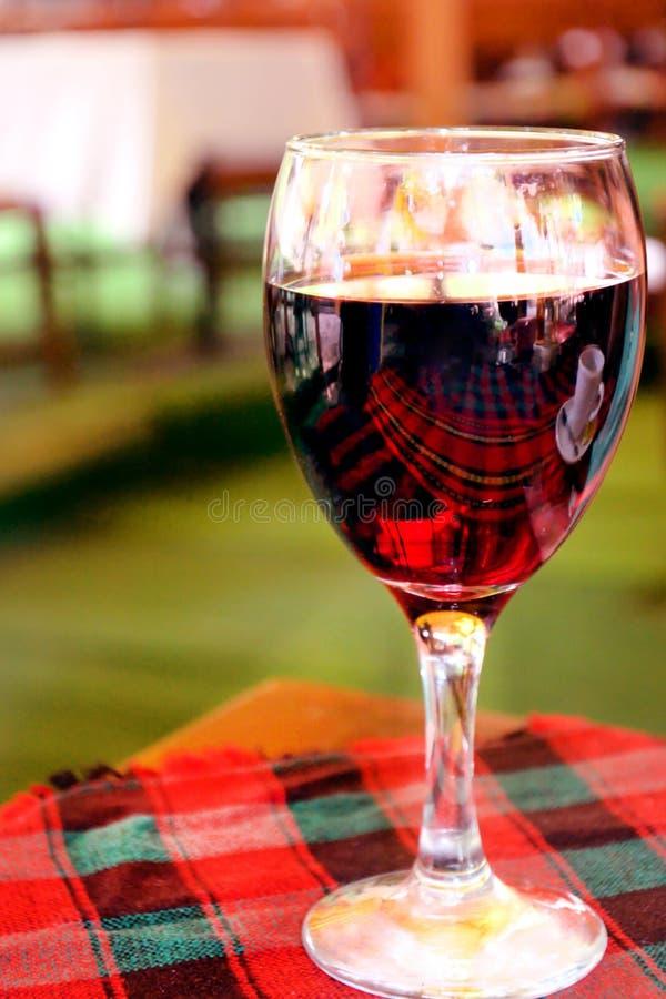 Rode wijn in wijnglas op de lijst met een tafelkleed in een restaurant eenzaamheid stock foto