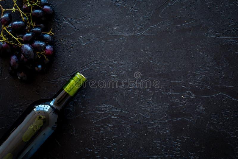 Rode wijnconcept Glasfles met drank dichtbij bos van druiven op de zwarte ruimte van het achtergrond hoogste meningsexemplaar stock foto
