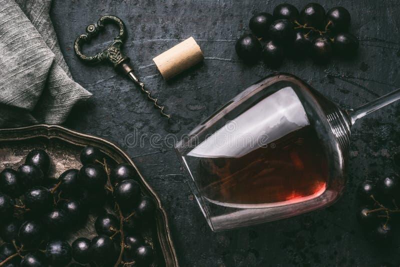 Rode wijnconcept met glas, druiven en uitstekende kurketrekker op donkere achtergrond stock foto's
