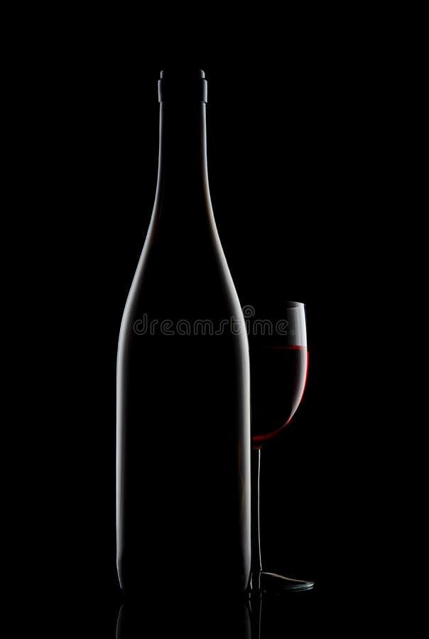 Rode wijnfles en wijnglas op zwarte achtergrond stock fotografie