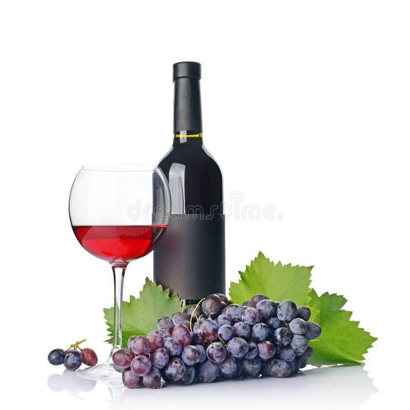 Rode wijnfles met leeg zwart etiket en glas voor het proeven met verse druif stock afbeeldingen