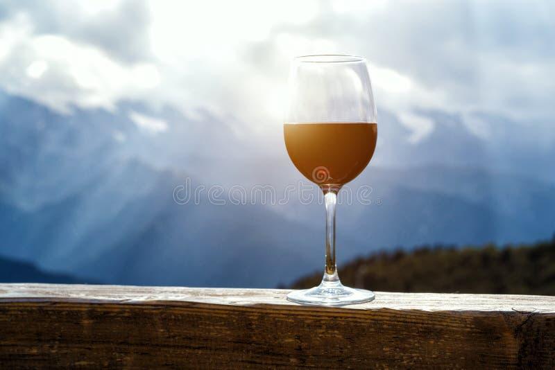 Rode wijnglas bij een picknick die zich op een houten lijst voor mooie bergachtergrond bevinden royalty-vrije stock afbeelding