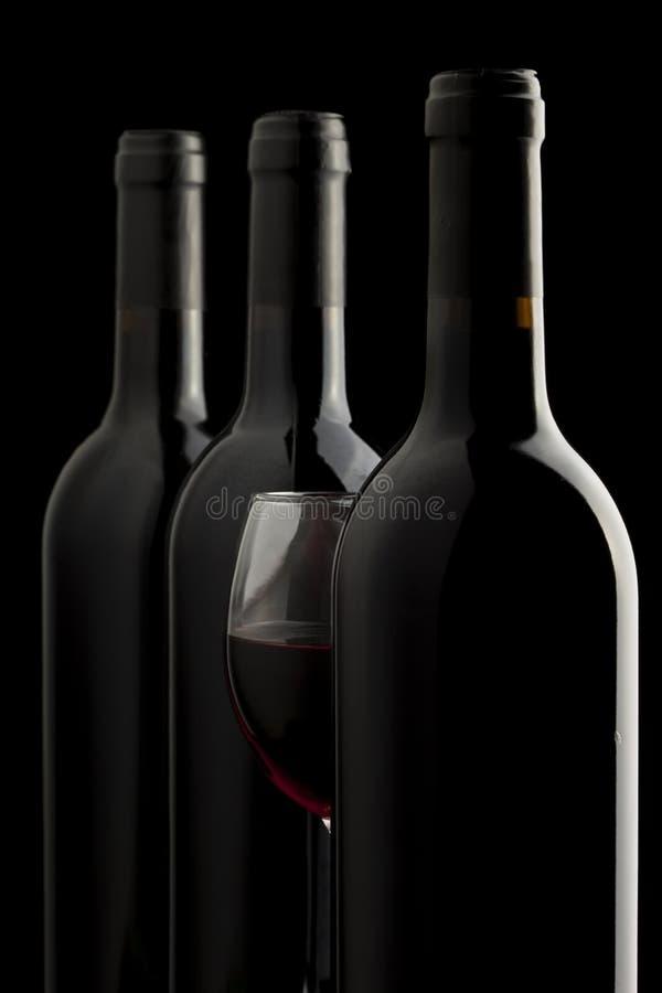 Rode wijnglas en een wijnflessen in zwarte backgro royalty-vrije stock fotografie