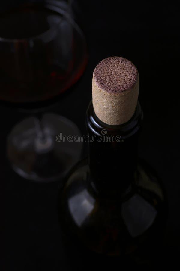 Rode wijnglas en wijnfles op zwarte achtergrond stock foto