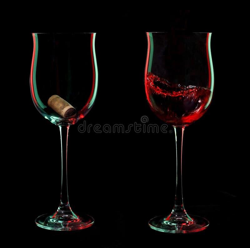 Rode wijnglazen met cork over zwarte achtergrond. stock foto