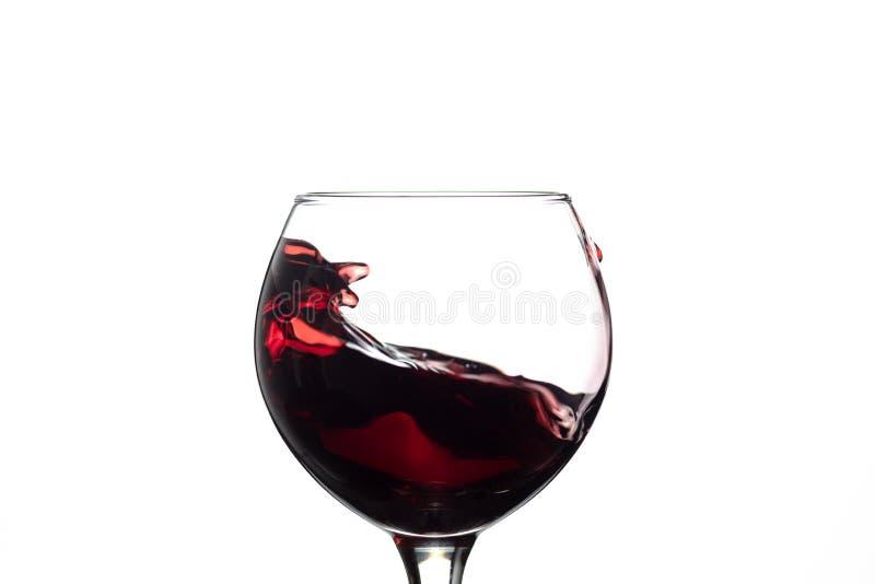 Rode wijnplons in glas op witte achtergrond royalty-vrije stock fotografie