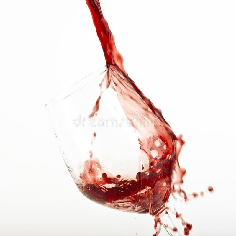 Rode wijnplons op een glas. stock afbeeldingen