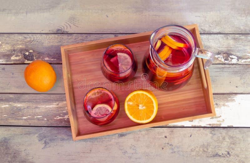 Rode wijnsangria met vruchten in glazen en waterkruik op houten dienblad met sinaasappelen dichtbij stock afbeeldingen