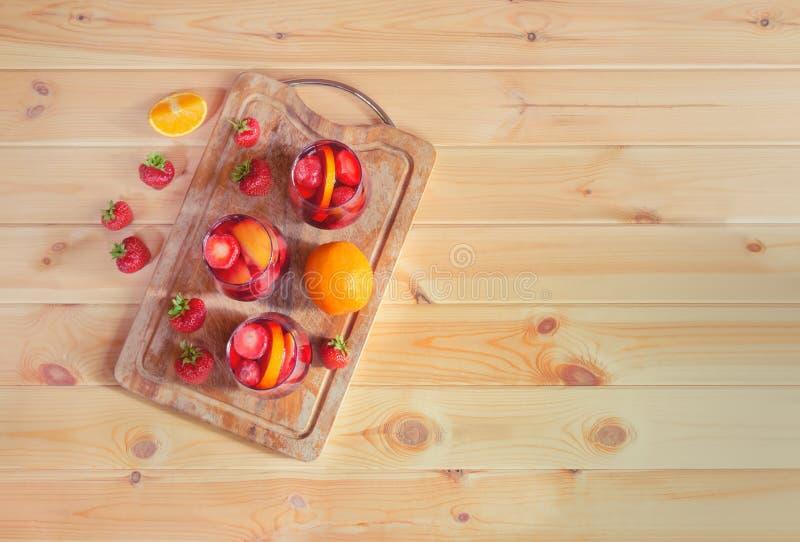 Rode wijnsangria met vruchten in glazen op scherpe raad Eigengemaakte verfrissende fruitsangria over rustieke houten lijst royalty-vrije stock afbeeldingen