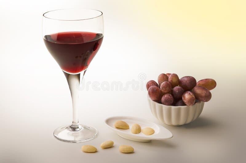 Rode wijnstok in een glas met amandelen en druiven stock fotografie