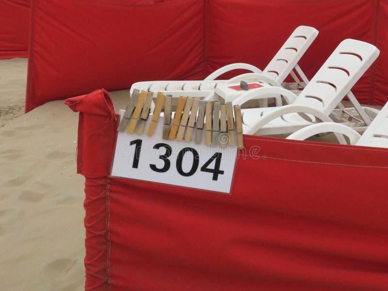 Rode windschermen en witte ligstoelen op het strand van Noordwijk stock foto