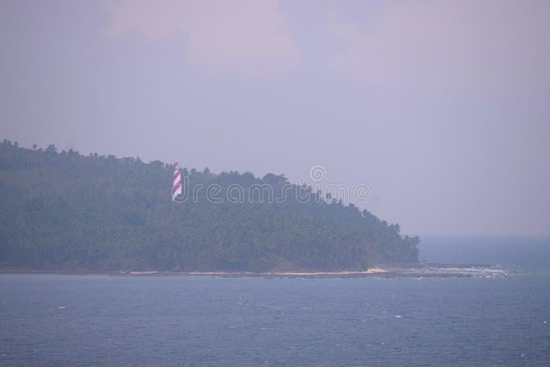 Rode Witte Vuurtoren in Bos op het Eiland van de het Noordenbaai met Oceaan en Bewolkte Hemel met Donderonweer - Andaman Nicobar, royalty-vrije stock foto