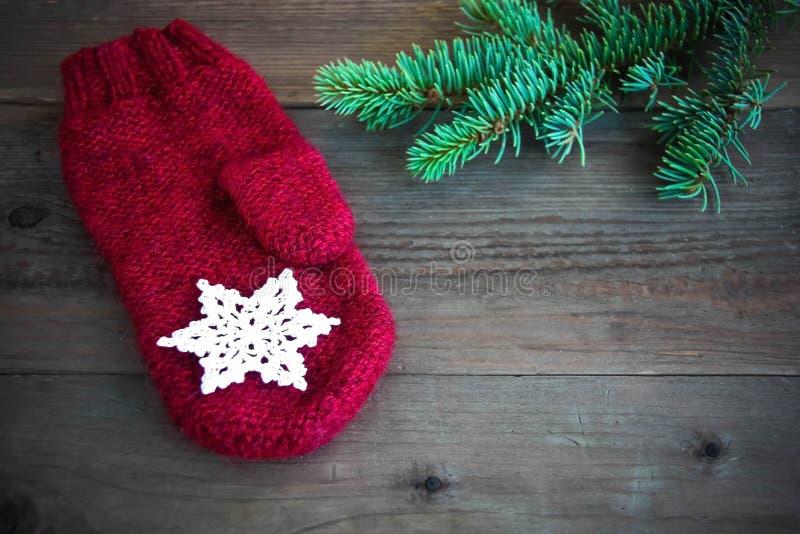 Rode wolvuisthandschoen met met katoen gehaakte sneeuwvlok dichtbij de groene boom van het Kerstmisbont op de rustieke houten ach royalty-vrije stock fotografie