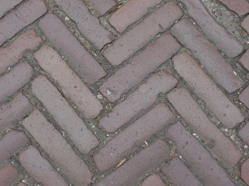 Rode zigzagstraatstenen op een straat stock afbeeldingen